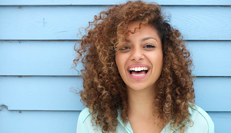 girl with curly hair shows off her dental veneers