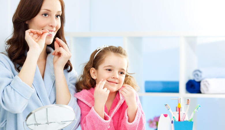 mom showing daughter about preventive dentistry and how to floss