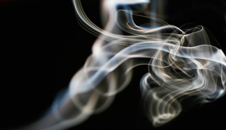 A wisp of tobacco smoke against a black background