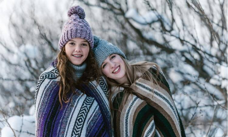 Two teenage girls, one with braces, stand next to each other wrapped in striped blankets and wear beanies in the snow