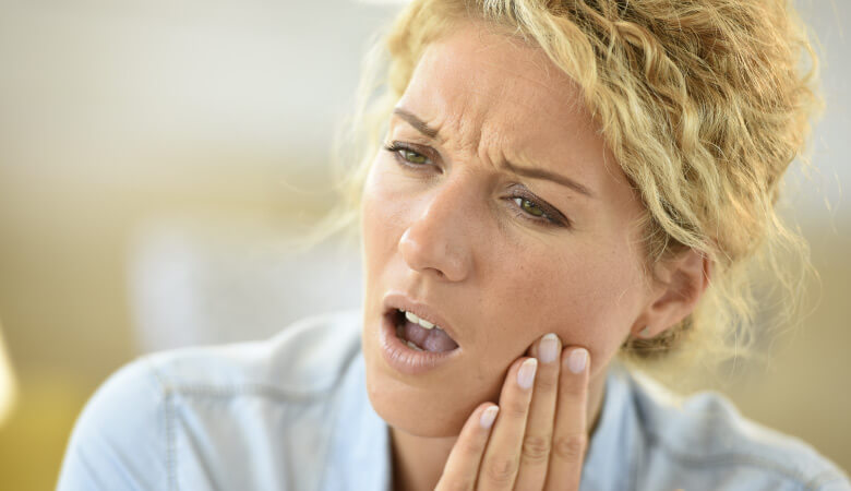 Blonde woman cringes and touches her cheek due to tooth pain from an advanced cavity