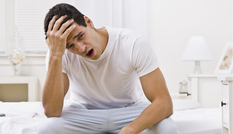 Man sleepily sits on the side of his bed yawning and touching his forehead