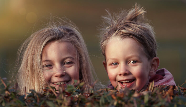 Closeup of a young brother and sister smiling behind a hedge after they've overcome their dental anxiety
