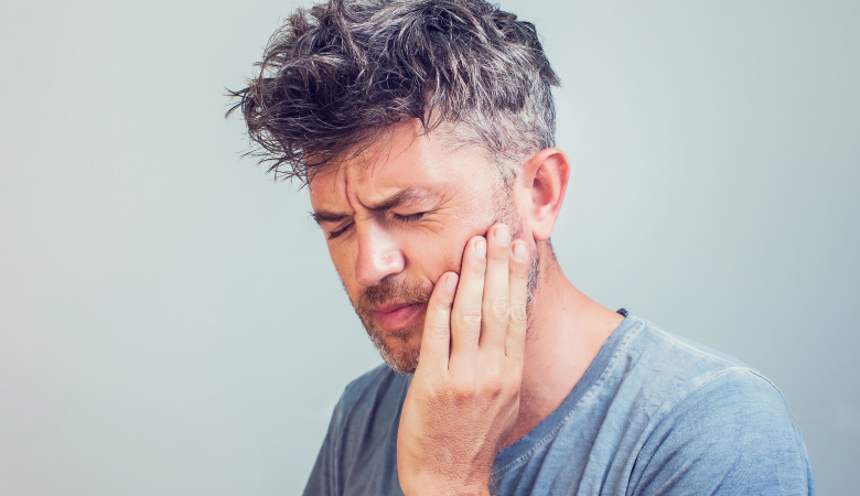 Middle-aged man wearing a gray shirt cringes and touches the side of his cheek due to sinus pain and tooth pain