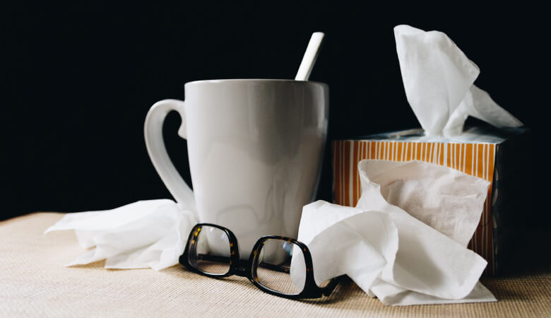 A box of tissues next to used tissues and a white mug when someone has the common cold