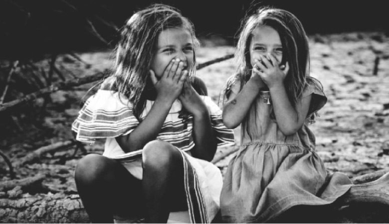 two young girls hold their mouths while laughing