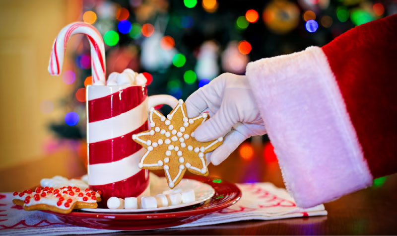 santa's gloved hand reaching for candy cane and cookies which can cause tooth decay