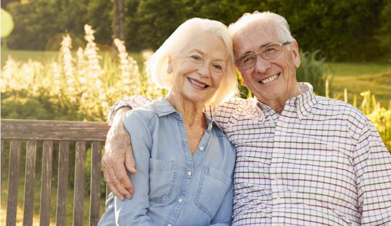 senior couple sitting on a bench smiling after learning how to clean their dentures