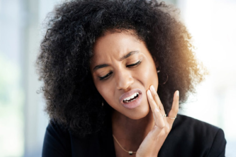dark haired woman holds her jaw in pain with an infected tooth