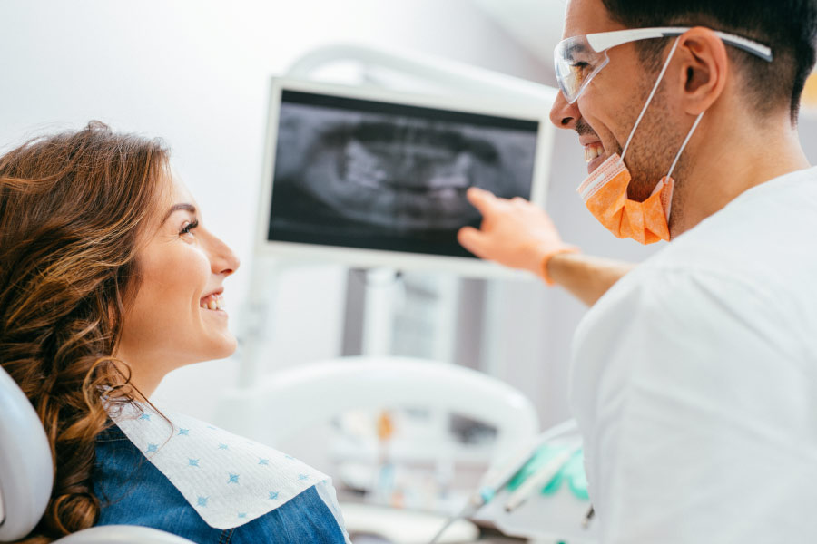 dentist shows a female patient her digital dental x-ray