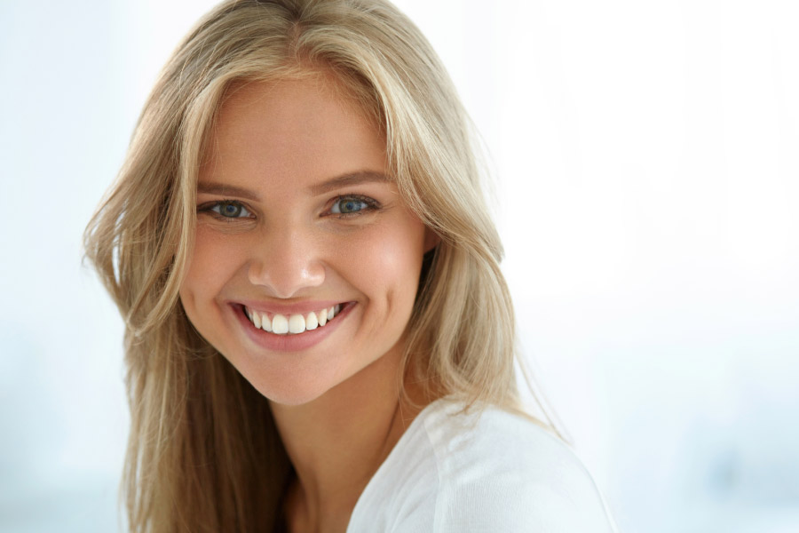 young woman smiles showing off her professionally whitened teeth