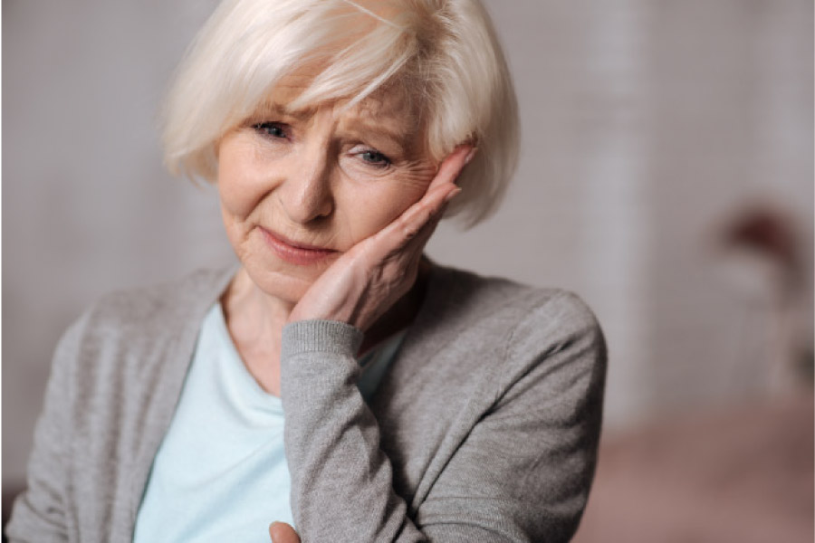 senior woman holds her jaw with sensitive tooth pain