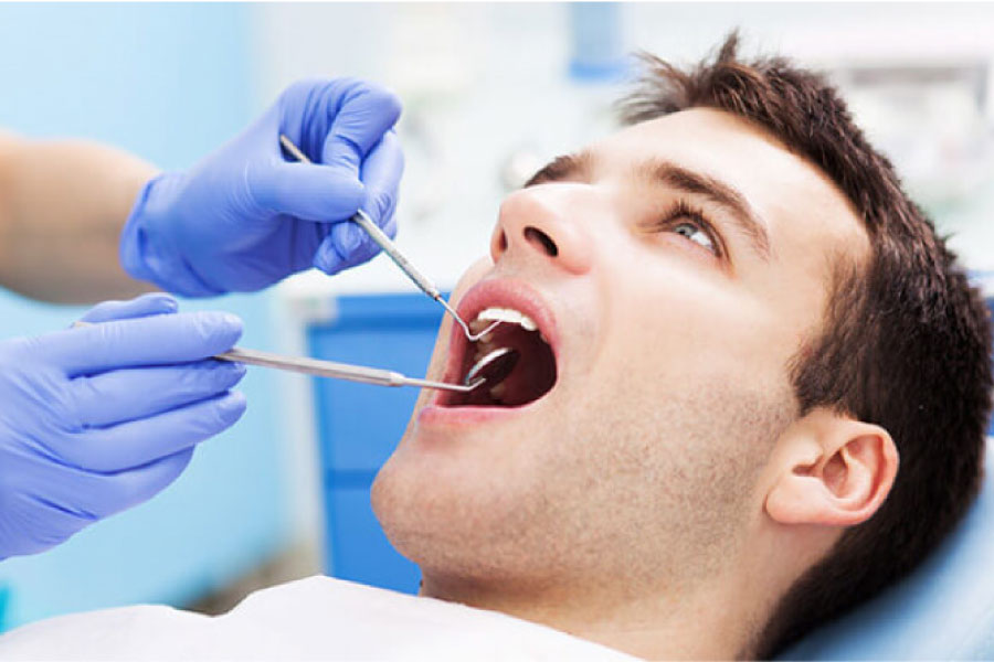 young man in the dentist chair getting an oral cancer screening